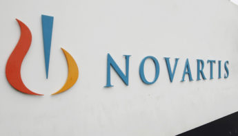 A man walks past the logo of Swiss drugmaker Novartis AG in front of a plant in Basel in this October 25, 2011 file photo. India's highest court will hear final arguments starting this week in a landmark case over drug patents that could change the rules for the country's healthcare sector and potentially curb its global role as a supplier of cut-price generic medicines, according to news reports on August 20, 2012. The Supreme Court hearing pits Swiss drugmaker Novartis AG against India's patent office, which has refused to grant a patent on the company's cancer drug Glivec on the grounds that it is not a new medicine but an amended version of a known compound. REUTERS/Arnd Wiegmann/Files (SWITZERLAND - Tags: BUSINESS HEALTH)